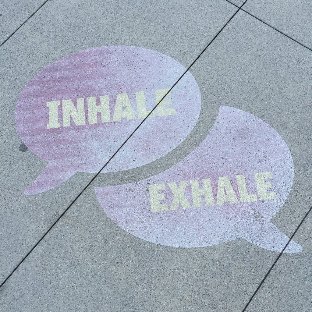 "Purple comment bubbles painted on sidewalk with instructions to breathe. Top one reads ""inhale"" and cuts into bottom one which reads ""exhale""."